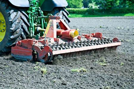 harrowing: A tractor pulls a harrow to work the land on a farm