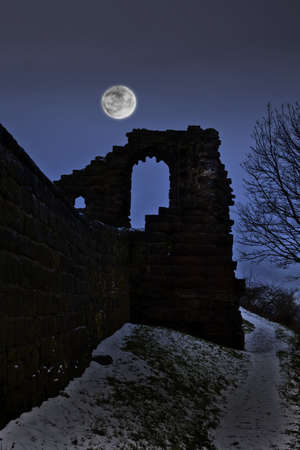 A very spooky castle in the moonlight after it has snowed photo