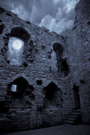 A very spooky Halloween castle in the moonlight, the moon is shining through a window.