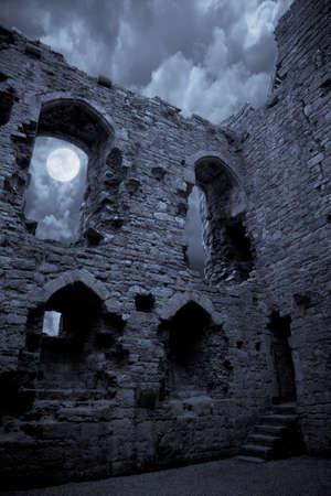 castello medievale: Un castello di Halloween molto spooky al chiaro di luna, la luna splende attraverso una finestra.