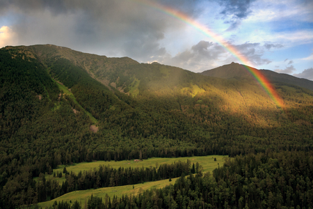 Bright Rainbow in the sky above Kanas Nature Reserve. Xinjiang Province, China. Clouds, alpine high altitude forest and fresh air. Altai Mountains near the border of, Kazakhstan, Russia and Mongolia.
