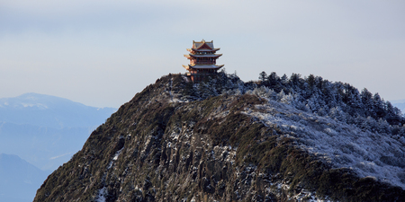 Emeishan, Mount Emei, Sichuan Province China. Sacred Buddhist Mountain. Snow Covered Mountain, Golden Chinese Buddhist temple in the snow. Winter scenery, ice and snow. Tall Pagoda, Viewing Platform