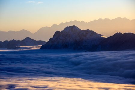 Sunset, Mountains and The Sea of Clouds - Snow Mountains in the distance protruding above a blanket of clouds like islands in an ocean - vibrant sunset sky, peaceful tranquility. Sunset above clouds