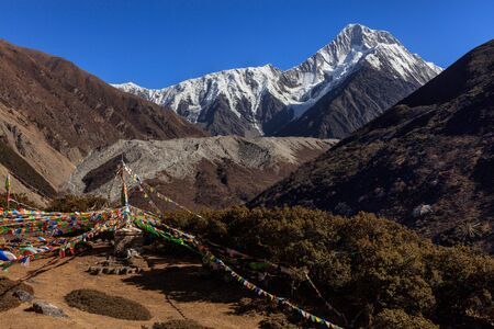 Mount Gongga (also known as Minya Konka) - Gongga Shan in Sichuan Province, China. Prayer Flags with Sacred Snow Mountain in the background. Himalayas, Highest Mountain in Sichuan Province China