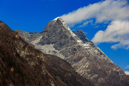 Four Girls Mountain National Park in Sichuan Province, China. ShuangQiao Valley Scenic Area, Snow Capped Jagged Mountains with clouds forming at the summit. Blue Sky, Snow Mountains, Siguniangshan