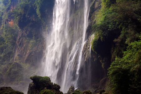Powerful Waterfall - Nature Background Images, Jagged RocksCliffs and Lush Green Trees. Fast Flowing Water, moss covered cliffs, mist, rocks in foreground. Malinghe Scenic Area in Xingyi, China