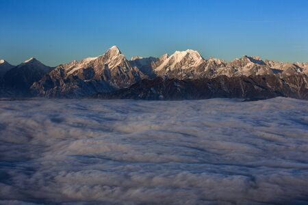 Edge of the Himalayas - view from Niubeishan Cattle Back Mountain in Sichuan Province, China. View on Clear day above the sea of clouds, blue sky. Himalayan snow capped high altitude mountains