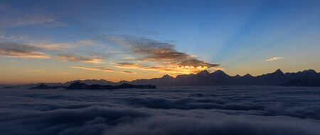 Minya Konka (Mount Gongga) view from Niubeishan Cattle Back Mountain in Sichuan Province, China. Vibrant Sunset, rays of sunshine, above the sea of clouds. Highest Mountain in Sichuan Province China.