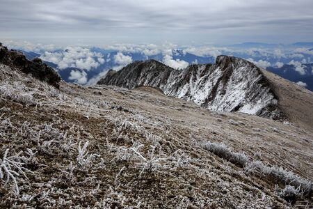 Mountains above the clouds, haze and fog. Mountain Landscape covered in Snow and Ice, Frost. Frigid cold atmosphere, frozen environment. Winter background, hiking trekking adventure. China Mountains