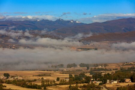 Countryside, Mist and Fog - Tibetan Farm situated in the grasslands of Western Sichuan Province, China. Colorful Tibetan building, agriculture farmland. High Altitude Plateau near Tibet, Ganzi