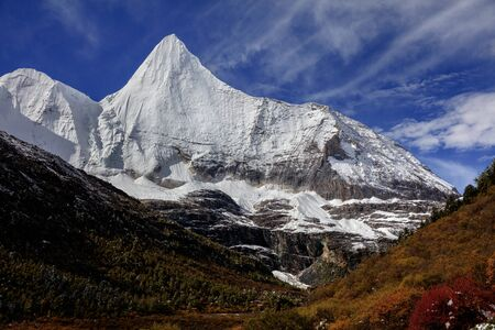 Jampayang, holy snow mountain in Daocheng Yading Nature Reserve - Garze, Kham Tibetan Pilgrimage region of Sichuan Province China. Alpine grassland in front of the towering ice summit of Yangmaiyong