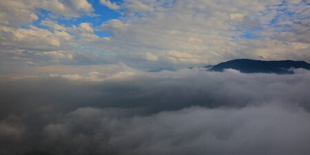 Abstract photograph above the clouds, sea of clouds effect, flying through the sky, aerial view, white puffy clouds and blue sky. Low pressure front atmospheric effect, cloudscape, cloudy weather