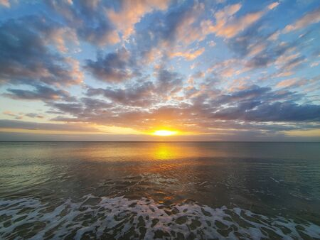 Abstract seascape panoramic background - Orange color in the sky, sunset late afternoon. Calm seasocean in the bottom of the frame. Minimalistic simple background image, blue and yellow colors.