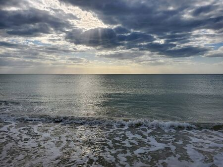 Abstract seascape panoramic background - late afternoon. Calm seasocean in the bottom of the frame. Minimalistic simple background image, blue and yellow colors, clouds and sky