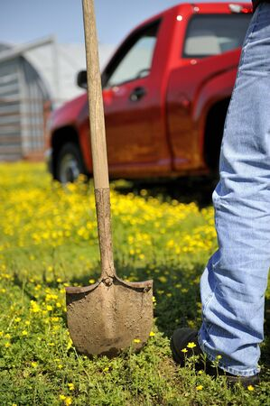 Farmer with a shovel standing in front of a red truck Stock Photo