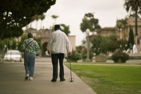 guy with walking stick: Senior ciizen couple walking together in a park Stock Photo