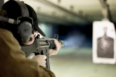 target shooting: Man shooting machine gun at a target at shooting range