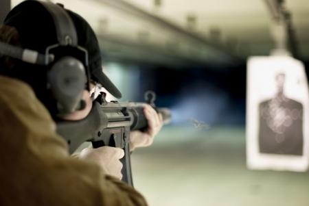 hand guards: Man shooting machine gun at a target at shooting range