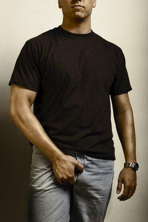 muscle shirt: Un macho adulto construido muscular agarra a s� mismo, vistiendo jeand y tshirt en blanco