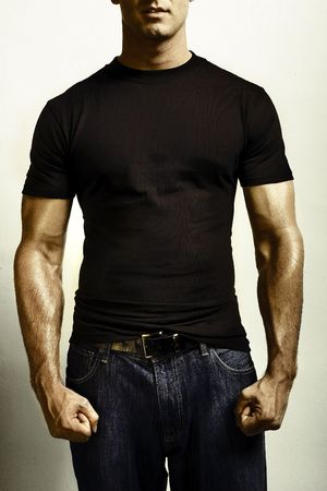 shirt template: A strong male adult flexing for camera in blank tshirt and jeans