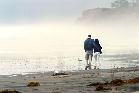 Young couple in love walking on a beach at sunset on a foggy day Stock Photo