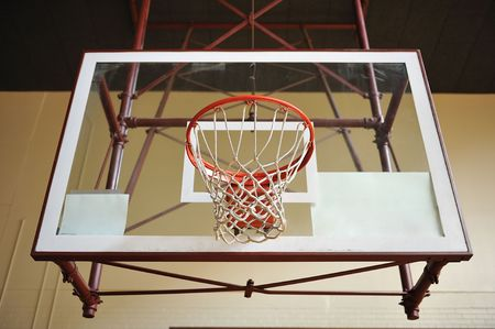 A basketball hoop with a glass backboard in an empty gym Stock Photo - 5373186