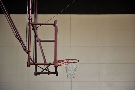A basketball hoop with a glass backboard in an empty gym