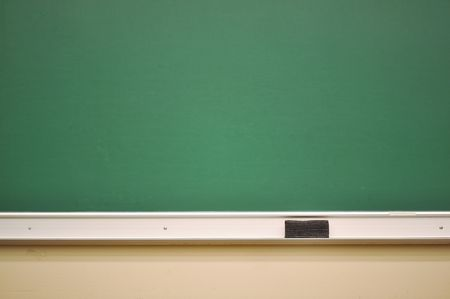 An empty chalk board with an eraser and chalk