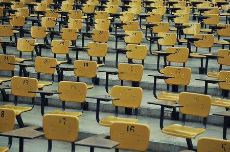 A large amount of empty seats with tables in a lecture hall