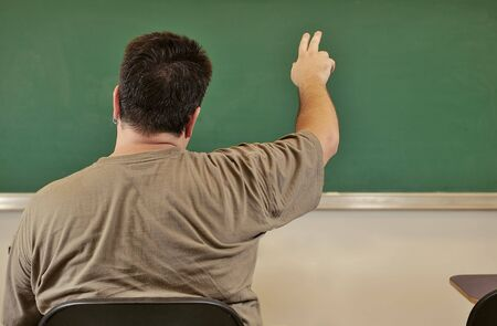 Student raising his hand in class infront of chalk board photo