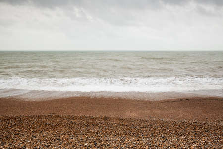 Atmospheric and Moody Long Exposure Photograph of Stoney Pebbled Beach and Sea at Brighton, East Sussex, England, UK.