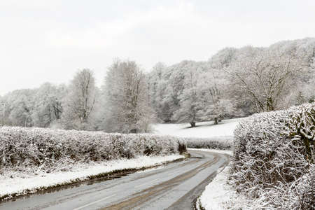 Hedge Lined Country Lane Surrounded by Snowy Fields in Winter, Penn, Buckinghamshire, England, UK.