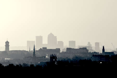Gotham Retro Photo Filter - London Cityscape at Sunrise with early morning mist from Hampstead Heath looking towards Canary Wharf, England, UK. 스톡 콘텐츠