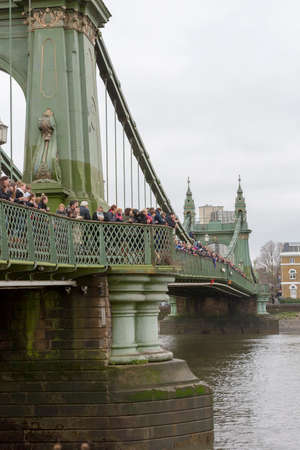 LONDON, 10 MARCH 2018: Spectators on Hammersmith Bridge waiting to watch the Womens Head of the River Race WEHORR 2018 on the River Thames, London, England UK