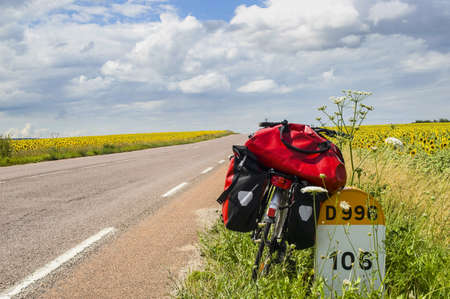 Bicycle with red bags, milestone, road and sunflowers fields in Burgundy  France  photo