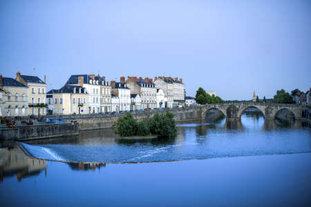 Laval  Mayenne, Pays de la Loire, France  - Ancient buildings and bridge on the river at evening