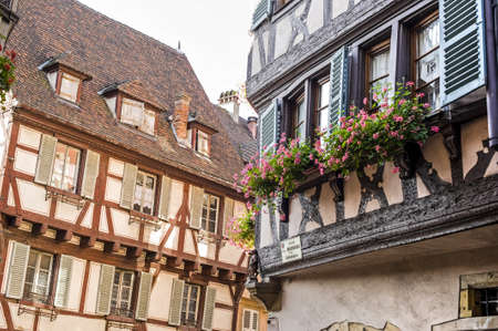 Colmar (Haut-Rhin, Alsace, France) - Exterior of old half-timbered houses with flowers at windows photo
