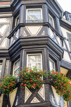 Colmar (Haut-Rhin, Alsace, France) - Exterior of old half-timbered house with flowers at windows photo