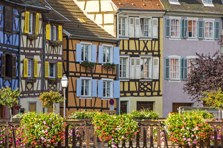 Colmar (Haut-Rhin, Alsace, France) - Exterior of old half-timbered houses and bridge with flowers in the Petite Venise Stock Photo
