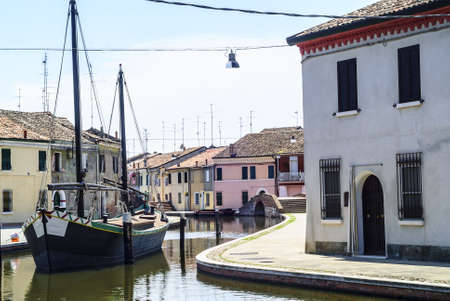 Comacchio (Ferrara, Emilia Romagna, Italy) - Winding canal with boat and colorful houses Stock Photo - 17269849