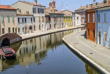 Comacchio (Ferrara, Emilia Romagna, Italy) - Winding canal with boat and colorful houses Stock Photo - 17272021
