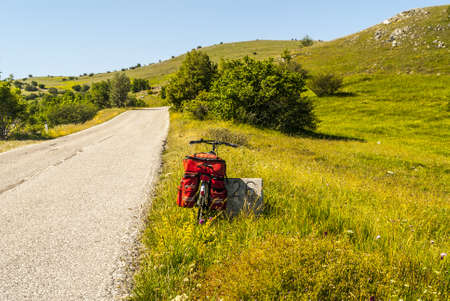 The road of Campo Imperatore (LAquila, Abruzzi, Italy) in the Gran Sasso dItalia natural park. A bicycle with bags photo
