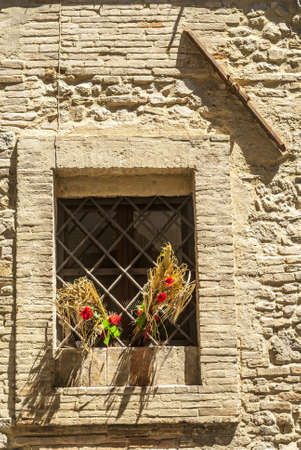 bevagna: Bevagna (Perugia, Umbria, Italy), Window with red flowers and tie-beam Stock Photo