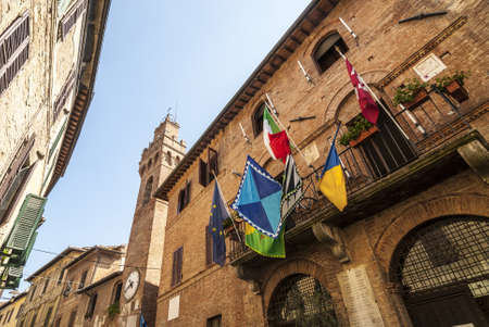 Buonconvento (Siena, Tuscany, Italy) - Historic buildings with clock tower and colorful flags Stock Photo