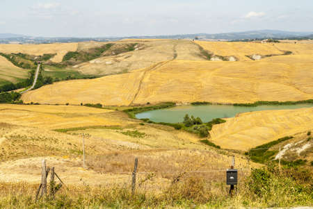 Crete senesi, characteristic landscape in Val d'Orcia (Siena, Tuscany, Italy) along the road from Asciano to Torre a Castello Stock Photo - 19160031