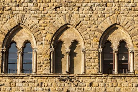 Volterra (Pisa, Tuscany, Italy) - Three mullioned windows of a medieval palace photo