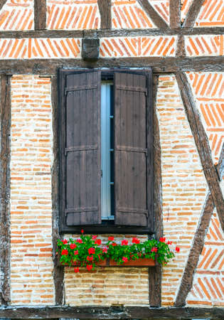 Lautrec (Tarn, Midi-Pyrenees, France), medieval village with half-timbered buildings: window with flowers photo