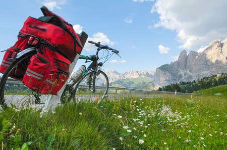 パッソ セッラ (ベッルーノ、ヴェネト州、イタリア、ドロミテ) 夏の山の風景: 赤いバッグを持つ自転車