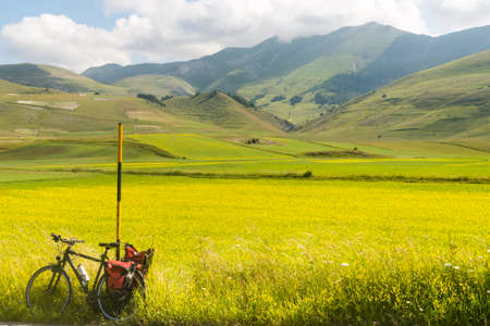 agriculture landscape: Piano Grande di Castelluccio (Perugia, Umbria, Italy), famous plateau in the natural park of Monti Sibillini. A bicycle with bags.