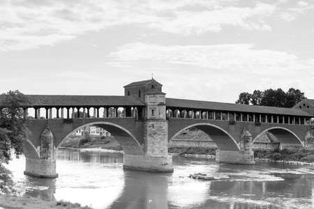 over white: Pavia (Lombardy, Italy): the famous covered bridge over the Ticino river. Black and white Stock Photo